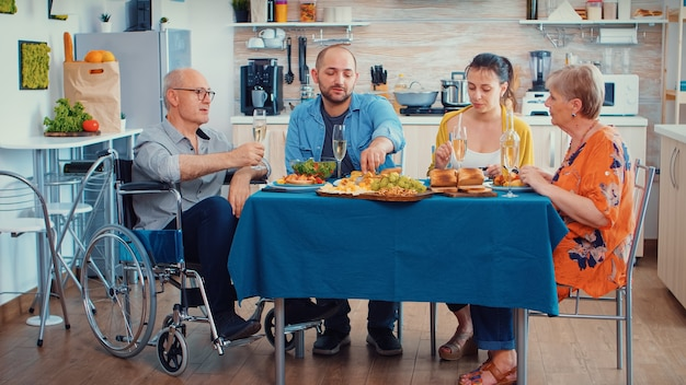 Grandfather with disability in whellchair and family having dinner. two happy couples talking and eating during a gourmet meal, enjoying time at home sitting around the table in the kitchen.