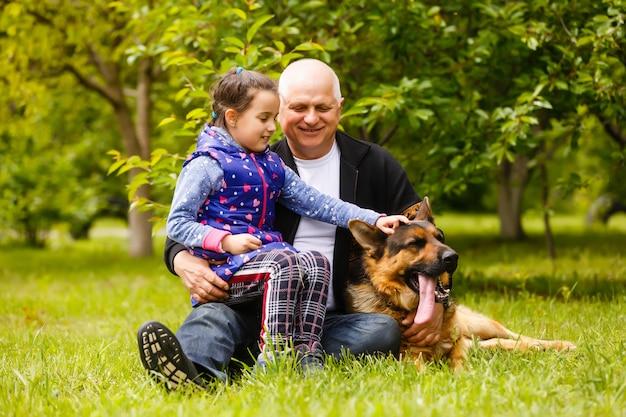 Дедушка с внучкой и собакой в саду