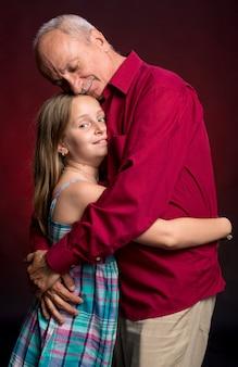 赤い壁に孫娘と祖父