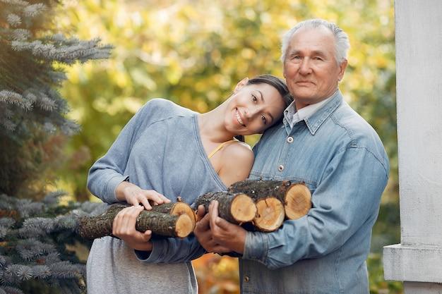 Nonno con nipote in un cantiere con legna da ardere in mano
