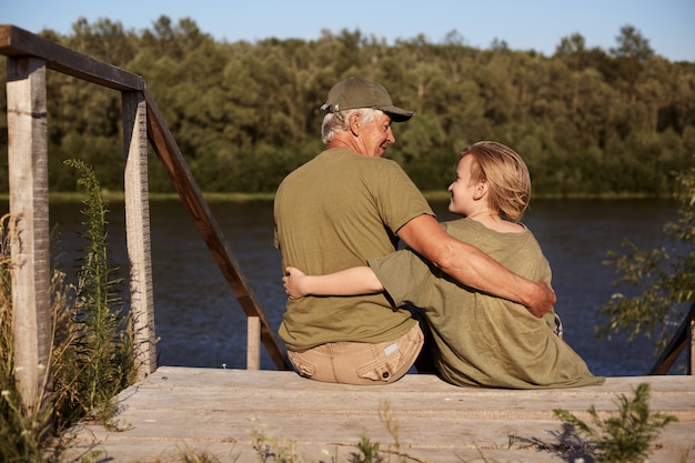 Grandfather with his little grandson enjoying walking outdoors, sitting on wooden setting near river and hugging