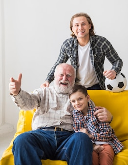 Дед с сыном и внуком смотрят игру
