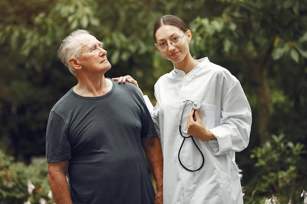 屋外の看護師に助けられた車椅子の祖父。公園の年配の男性と若い介護者。
