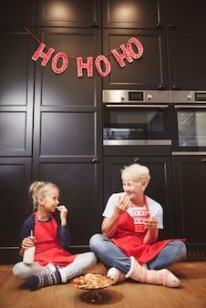할머니와 집에서 만든 된 쿠키를 먹는 귀여운 여자