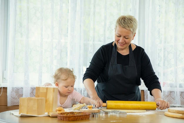 Бабушка и внучка раскатывают тесто на присыпанном мукой деревянном столе. понятие семейных традиций. концепция единения. концепция урок домашней выпечки. концепция видеоблога