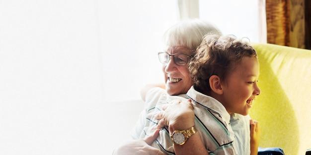 社会的な距離のデザインスペースの後に抱き締めるおばあちゃんと孫