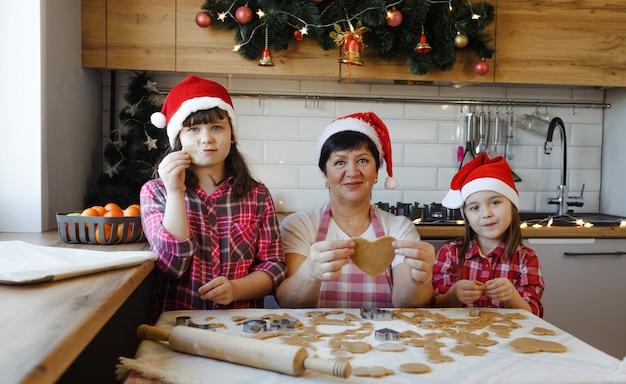 Бабушка с внучками пекут печенье на кухне. семейные традиции