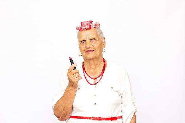 Бабушка наносит помаду, старая модная дама с бигуди и губной помадой