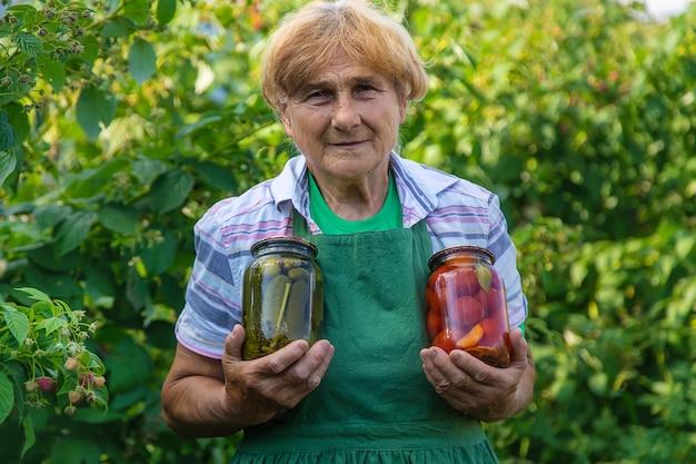 할머니는 겨울 동안 토마토와 오이를 통조림으로 만들었습니다. 선택적 초점입니다. 음식.