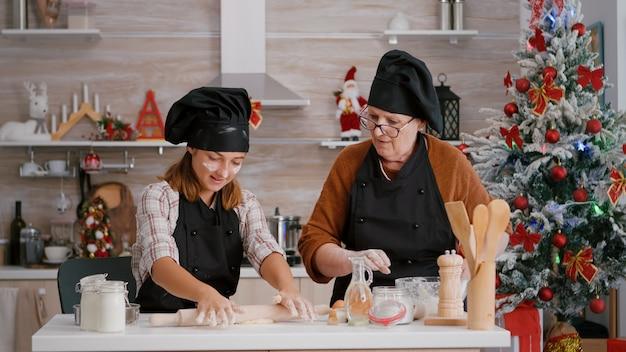 おばあちゃんのコーヒー孫が料理のキッチンで自家製ジンジャーブレッドデザートを準備する