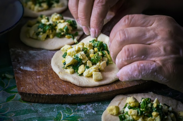 おばあちゃんはパイを作ります。家庭料理。女性の手にある生地のオメメイドケーキ。手作業でパイ生地を作る工程