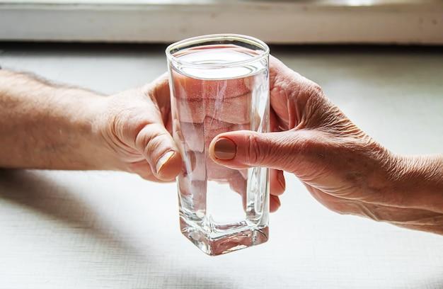 おばあちゃんはおじいさんにコップ一杯の水を与えます。セレクティブフォーカス。食物。