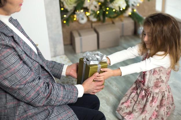 Бабушка дарит внучке подарок на рождество