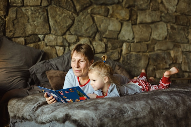 Grandma and granddaughter in christmas pajamas reading a book, lying on the bed in the chalet. family christmas .