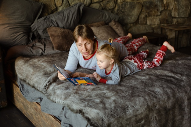 Grandma and granddaughter have fun together reading a book on the bed