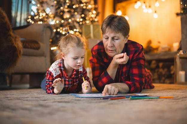 Grandma and granddaughter lie on the carpet in front of the christmas tree and draw.