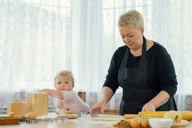 Grandma and granddaughter make dough on wooden table with flour. family traditions concept. togetherness concept. homemade baking lesson concept. blogging concept