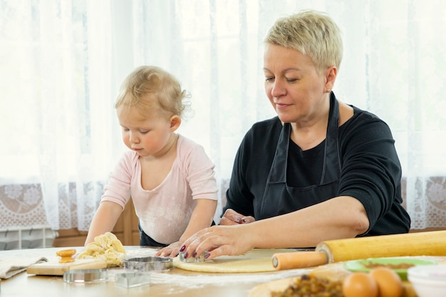 Grandma and granddaughter slices sheet of dough with cookie mold baking lesson