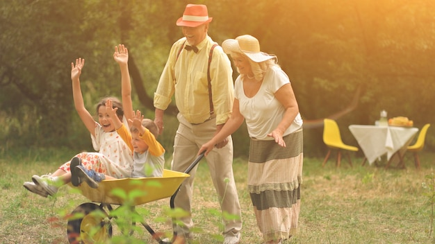 Grandma and grandpa are pushing their grandchildren in a wheelbarrow