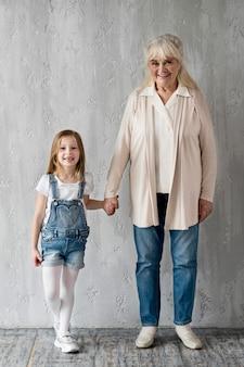 Grandma holding little girl hand