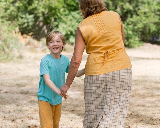 Nonna e bambino che tengono le mani all'aperto
