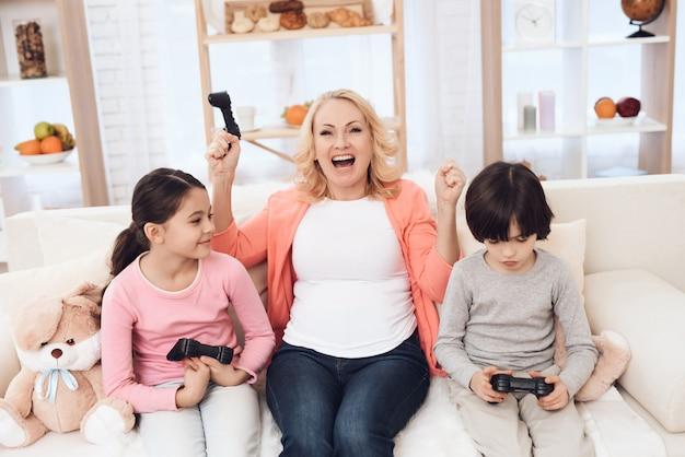 Бабушка играет в видеоигры с внуками