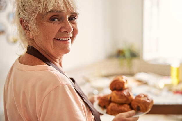 그녀의 특별한 집에서 구운 음식과 함께 포즈를 취하는 할머니