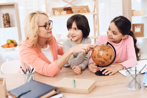 Grandma showing place on globe doing homework