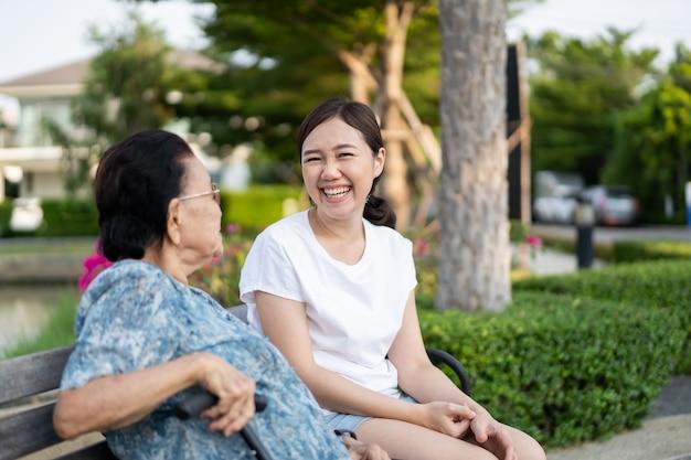 公園で孫娘の横に座っているおばあちゃん。家族の中で年配の人の世話をしている若い女性。ウェルネス、ウェルビーイング、ヘルスケアのコンセプト。