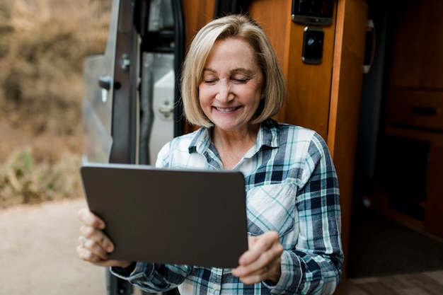 Бабушка сидит в автофургоне, глядя на свой планшет