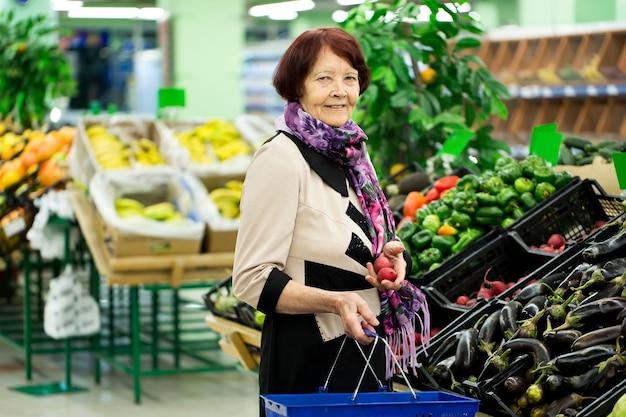 おばあちゃん、老婆はスーパーで大根を選びます。