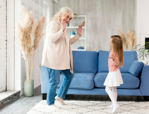 Grandma with girl at home playing