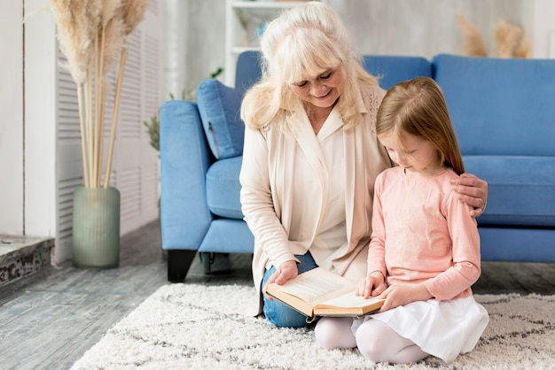 Grandma with girl at home reading