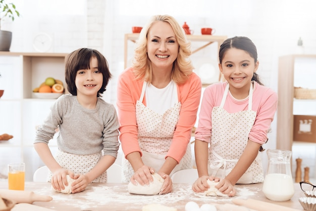 Grandma with kids kneading dough for cookies