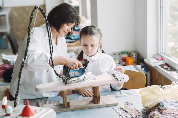 Бабушка с маленькой внучкой гладит одежду на фабрике
