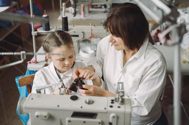 Бабушка с маленькой внучкой шьют одежду на фабрике