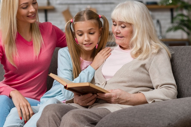 Бабушка и семья сидят на диване и читают книгу