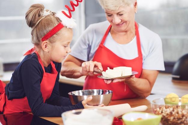 祖母と孫娘がキッチンで料理をする