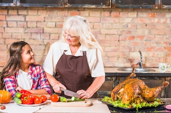 Grandmother and granddaughter cooking turkey in kitchen