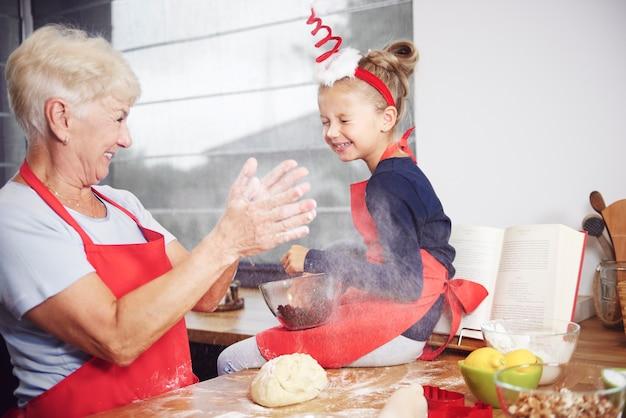 祖母と孫娘がキッチンで楽しんでいます