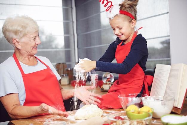 一緒にクッキーを作るのを楽しんでいる祖母と孫娘