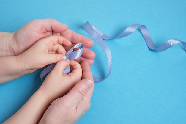 할머니와 손녀는 파란색 배경, 아이의 손과 여자의 손, 복사 공간, 당뇨병 및 암 기호에 파란색 리본을 잡고