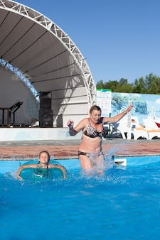 プールの祖母と孫娘若い祖母と孫娘は喜んでthに飛び込みます...