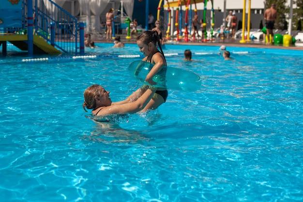 Бабушка и внучка в бассейне молодая бабушка закидывает девочку в надувной круг ...