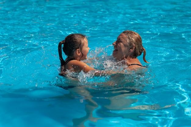 プールの祖母と孫娘。晴れた日、週末のアクティビティでは、陽気な祖母と孫娘がウォーターパークのプールに水滴をはねかけます。