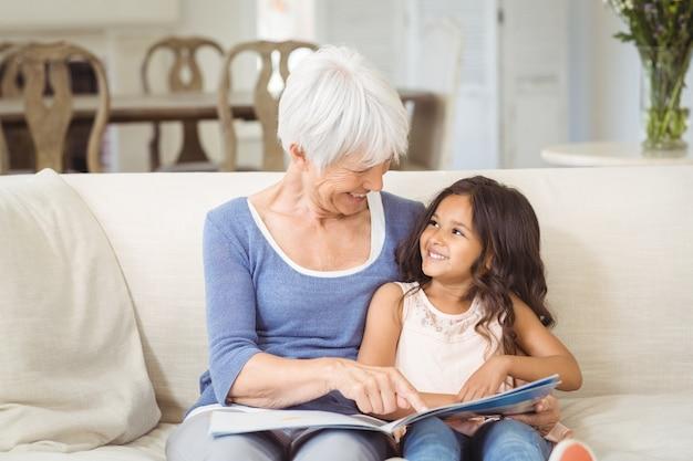 Бабушка и внучка общаются, глядя на фотоальбом в гостиной