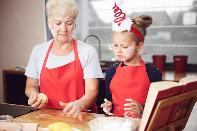 祖母と孫娘がキッチンで生地を作る