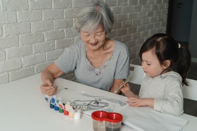 祖母と孫娘が家を水彩で描く。祖母は孫娘に絵の具を塗ることを教えています。曾祖母と孫が一緒に描いている