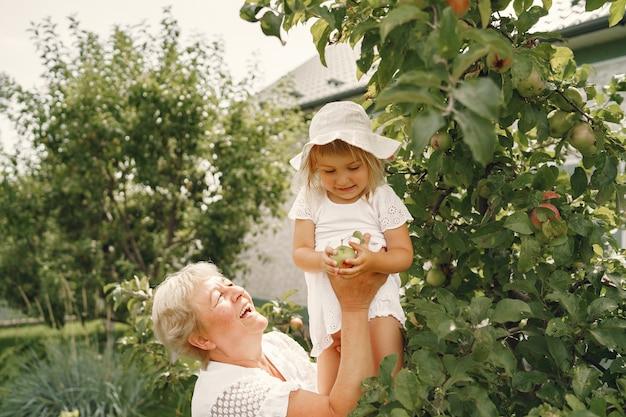Бабушка и внучка вместе обнимаются и радостно смеются в цветущем абрикосовом саду в апреле. семейный образ жизни на открытом воздухе.