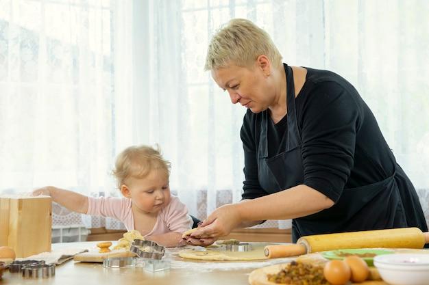 祖母と孫娘がクッキーカッターを使って生地を形に切る